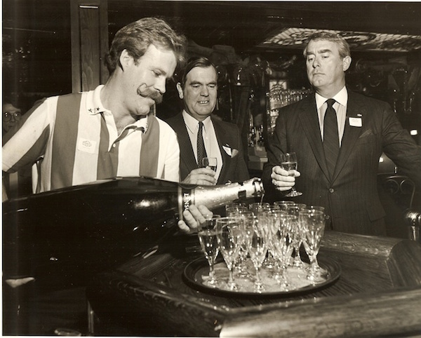 Dan Scoggin, right, watches a bartender pour champagne from a giant bottle. (Via Friday's Founder)
