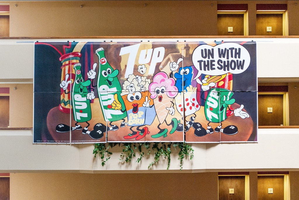"1971's ""Un With the Show"" is one of the billboards Bob Treat and his high school friends hung in the atrium of University Plaza Hotel in Springfield, Missouri, for the Glendale High Class of '71 reunion. The billboard, credited to Ray Lyle, features the same characters seen in 7Up's 1971 ""7Up Go On Out to the Lobby"" movie intermission film. (Courtesy of Bob Treat)"
