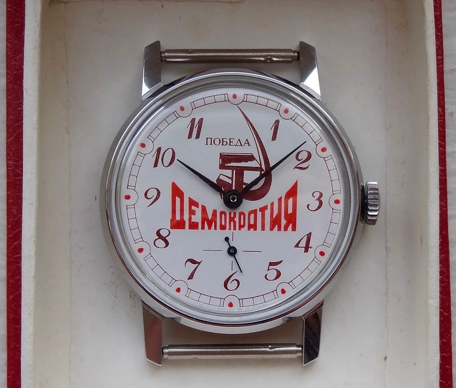 "As the USSR's economy weakened, more watches were made with kitschy nationalist imagery, like this Pobeda from the 1980s featuring the word ""Democracy"" below a hammer and sickle."