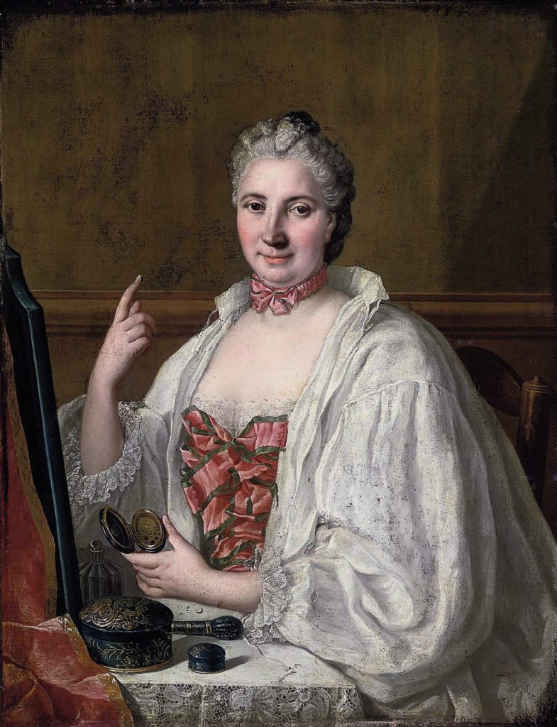In her 18th-century portrait, Anne de la Grange-Trianon fixes viewers with her conspiratorial gaze just as she prepares to apply a beauty patch. Via Wikimedia. (Click to enlarge)