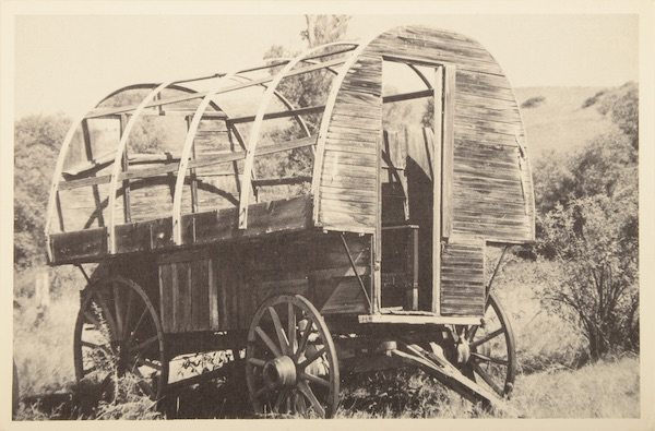 "This tourist postcard labeled ""Montana Sheepwagon, Sheepherder's Mobile Home"" shows an early wagon with a house-sized door. (From Don't Call Them Trailer Trash, courtesy of Schiffer Publishing)"