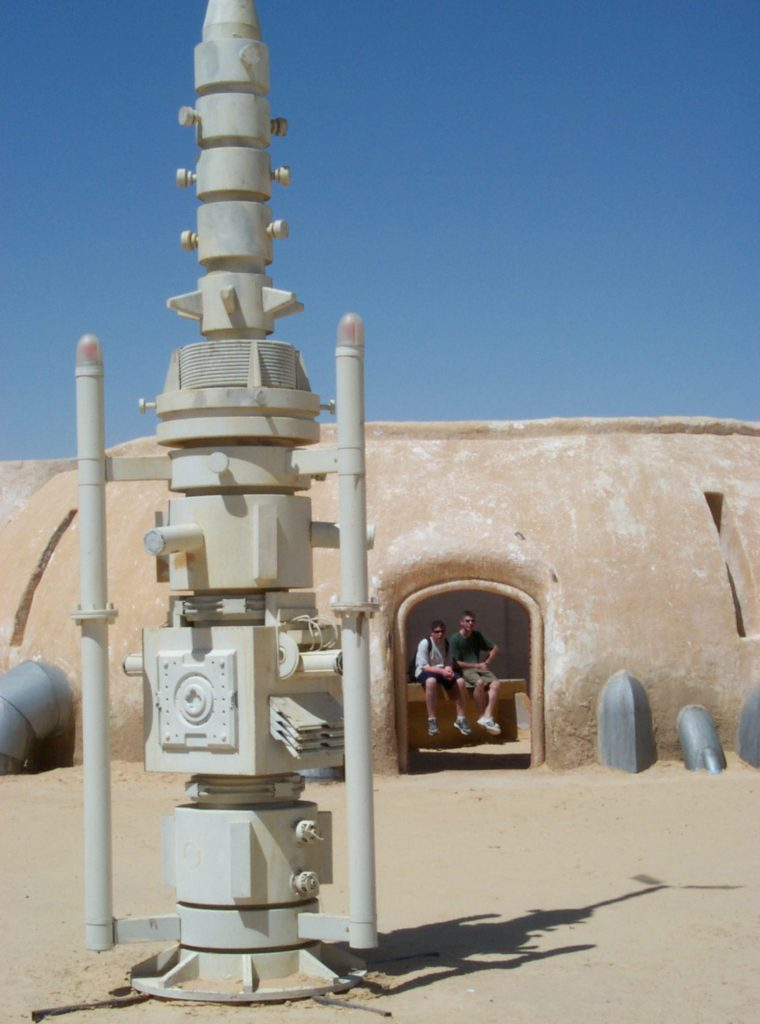 "Alinger and his younger brother sat in Watto's parts shop (made of wood and plaster) on the set of Mos Espa near Tozeur, Tunisia, in 2001, just a few months after the second prequel finished filming there. In the foreground is a moisture-vaporator prop (made of wood) that, in the movie, was used to supply water to the desert planet. This set, a popular tourist site seen in ""The Phantom Menace"" (1999) and ""Attack of the Clones"" (2002), is now threatened by sand dunes. (Courtesy of Brandon Alinger)"