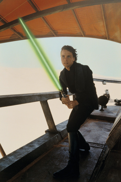 "Luke Skywalker holds Obi-Wan's lightsaber on the barge based on Commodore Tompkins' model in a still from ""Return of the Jedi."""