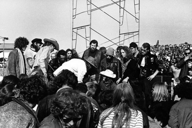In 1969, when a free Rolling Stones concert at the Altamont Motor Speedway turned violent due to the overly aggressive policing of the show by members of the Hells Angels, who'd been hired as security, Marty Balin (at center, in white hat) stepped into the fray to stop a member of the gang from beating up a fan. He was knocked unconscious for his trouble. Courtesy Robert Altman.