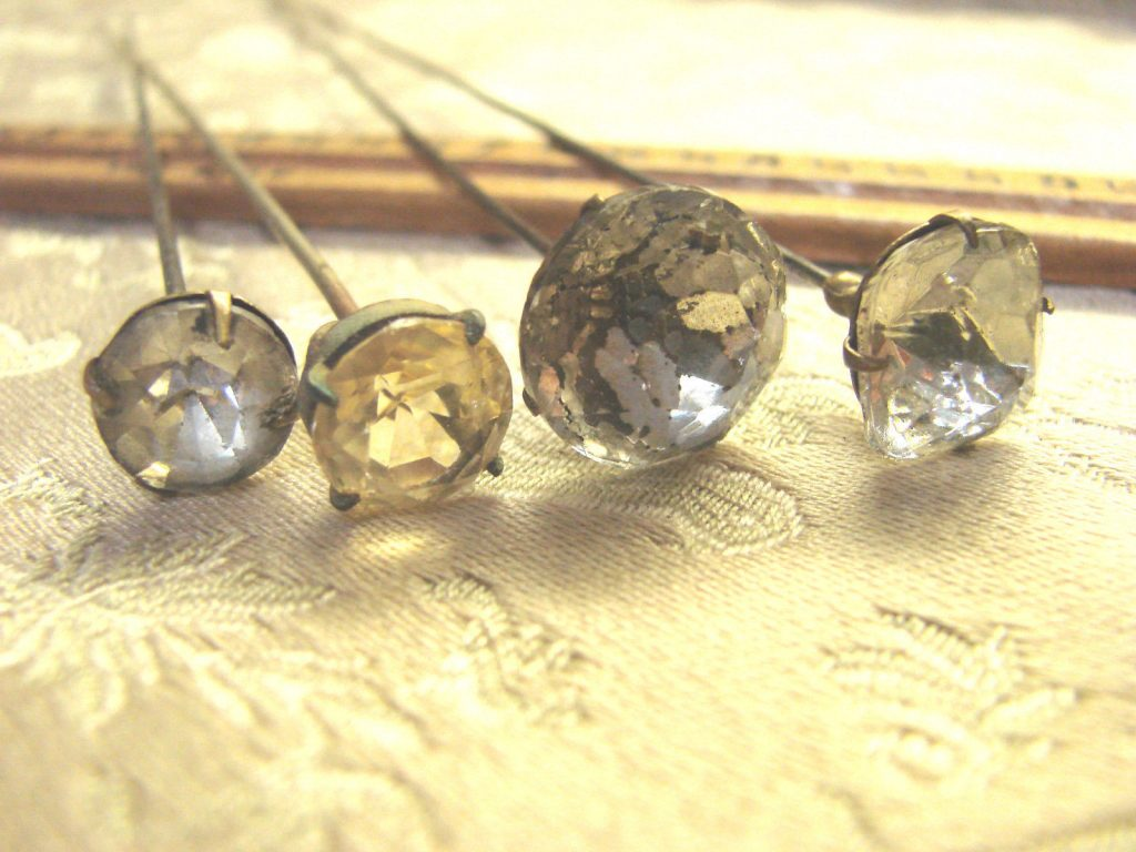 A group of four antique hatpins, 6-8 inches long, with cut-glass rhinestones on the heads. (Via eBay)