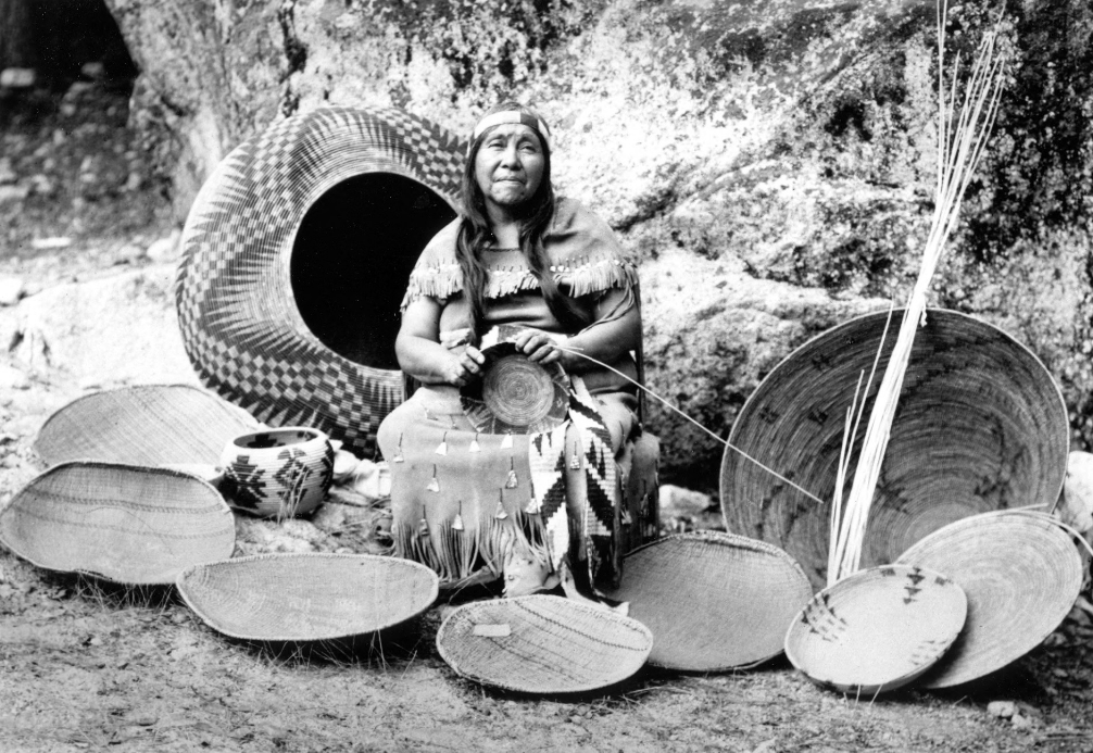 Lucy Telles with her baskets in Yosemite National Park, circa 1940s. Via the Yosemite Museum, National Park Service.