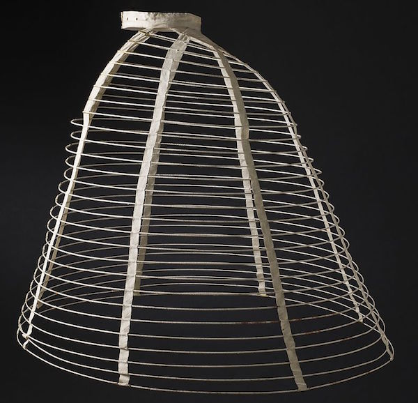 This 1865 cage crinoline is made from cotton-braid-covered steel, cotton twill and plain-weave double-cloth tape, cane, and metal. (From the Los Angeles County Museum of Art, via WikiCommons)