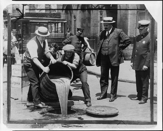 New York City Deputy Police Commissioner John A. Leach, right, watches agents pour liquor into sewer following a raid during the height of prohibition in the 1920s. (Via Library of Congress)