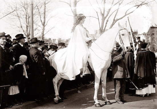 Labor lawyer Inez Milholland led the first Women's Suffrage Procession on horseback in a dramatic white costume on March 3, 1913, in Washington, D.C. Angry men looked on as thousands of women marched for voting rights. (Via Library of Congress)