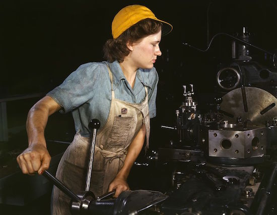 During World War II, a woman—known as a Rosie the Riveter—operates a turret lathe to machine parts for wartime transport planes at the Consolidated Aircraft Corporation plant in Fort Worth, Texas. (Via Library of Congress)