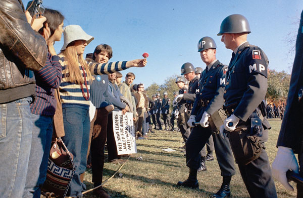 A female demonstrator offers a flower to military police on guard at the Pentagon during an anti-Vietnam protest in D.C. in October 1967. (Via the National Archives)