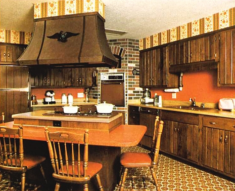 An early '70s kitchen in Arizona with a patriotic eagle, Knotty Pine cabinets, modified Windsor chairs, and a Harvest Gold and Burnt Orange color palette. (Via Ugly House Photos)