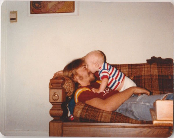 A young dad cuddles with his baby on a Colonial Revival sofa with a brown Herculon plaid fabric in this 1979 vernacular photo. (Via eBay)