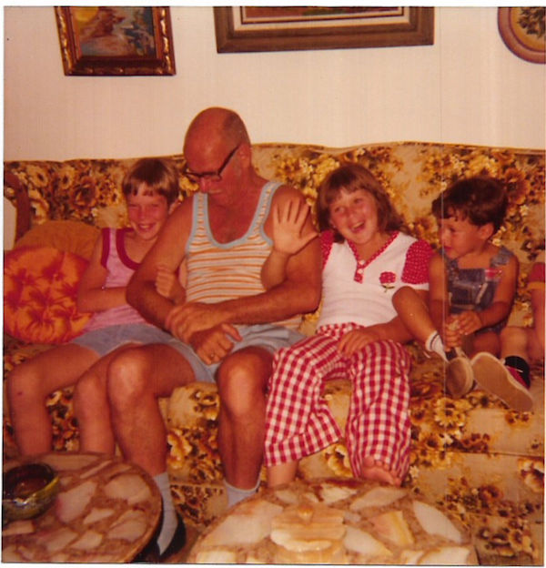 A found snapshot from 1977 shows a grandpa hanging out with his grand kids on a brown-tone floral Colonial-style couch. (Via eBay)