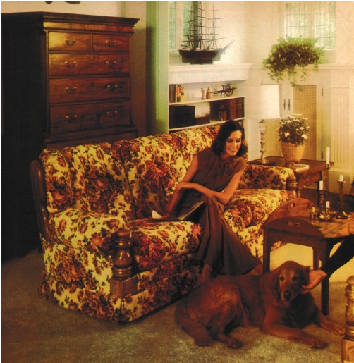 In this 1970s ad, a stylish young woman on a floral Grandma couch while an unseen companion pets her golden retriever on shag carpeting surrounded by Colonial Revival furniture. (Via The Giki Tiki)
