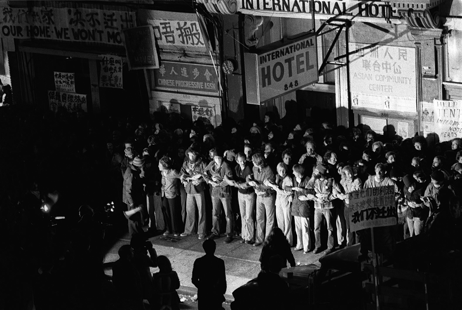 Protestors block the police department from forcibly evicting tenants of the International Hotel in 1977. Via Wikimedia. (Click to enlarge.)