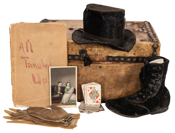 "A diminutive overnight trunk owned by Tom Thumb and his wife, Lavinia, circa 1870, as exhibited at the Freakatorium Museum. Items within the trunk include two of Lavinia's unmatched gloves as well as one high black shoe, a Tom Thumb-owned leather glove, his top hat, a partial deck of miniature playing cards, Lavinia's copy of the play ""All Tangled Up,"" and a hand-colored CDV of Tom and Lavinia Thumb and their child. (Courtesy of Potter & Potter Auctions)"