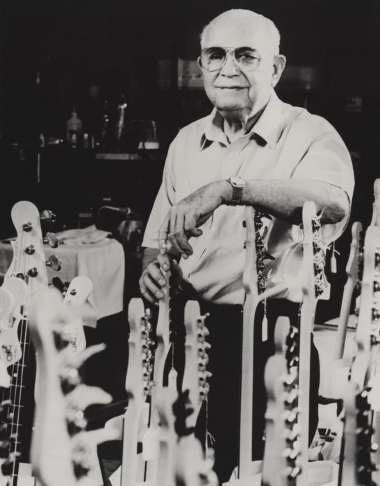 Leo Fender amid numerous Fender electric guitars.