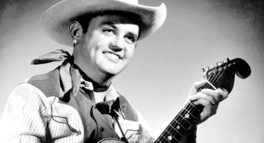 Merle Travis holding his Bigsby guitar, which is easily identifiable thanks to its distinctive headstock.