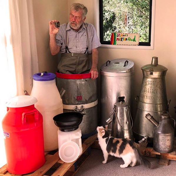 Ian Spellerberg with his cat Florence. Spellerberg is standing in a 25-gallon can and hold a tiny example meant for just an eight of a pint.