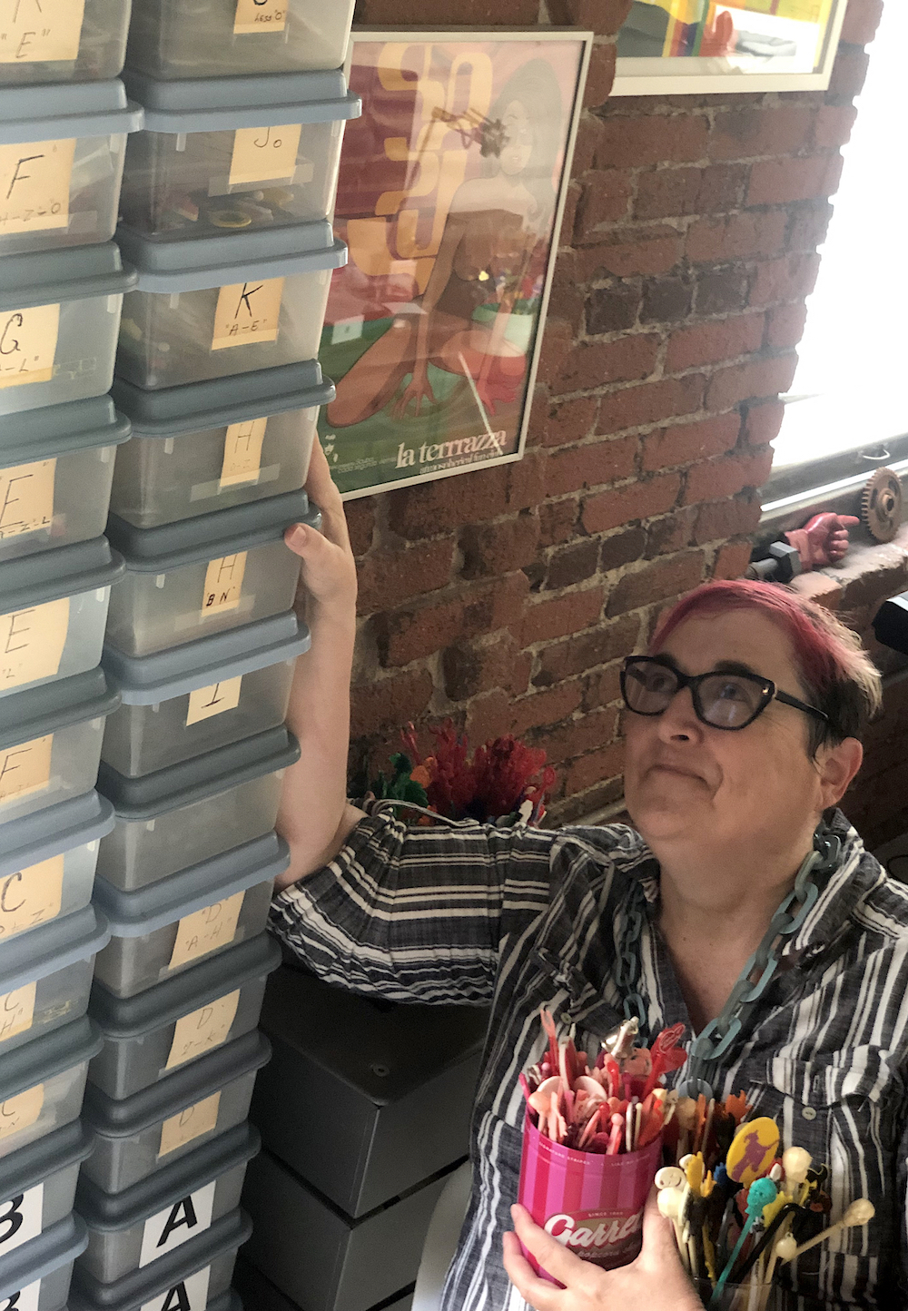Ashlund with just a few of the 100 or so Tupperware boxes she uses to store her collection of 50,000 swizzle sticks.