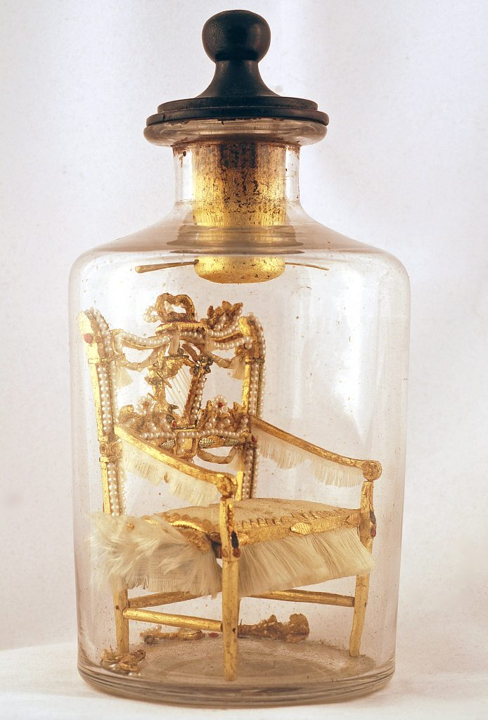 A European bottle whimsey featuring a miniature golden chair in a bottle with a pontil mark, c. 1890-1900.