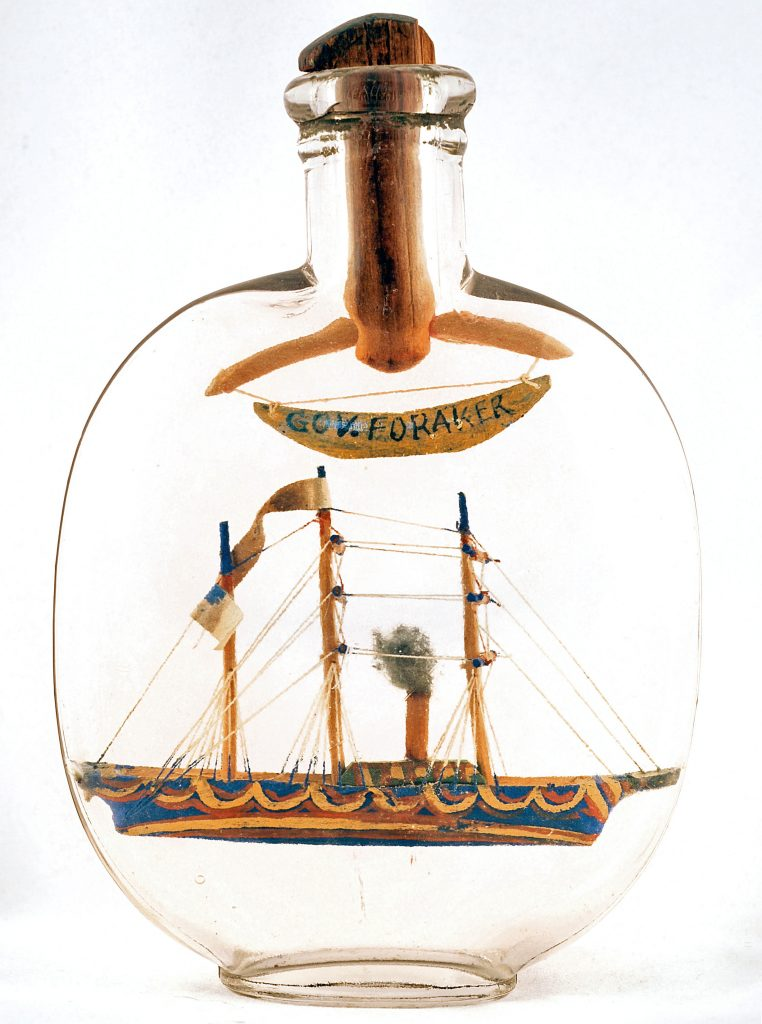 "A tiny ship in a ""pumpkinseed"" flask (named for its shape) with a banner commemorating Ohio Governor Joseph Benson Foraker, c. 1886-1890. This whimsey bottle was made at the Soldier's Home in Dayton, Ohio, a home for disabled veterans of the Civil War. Photo courtesy Susan D. Jones."