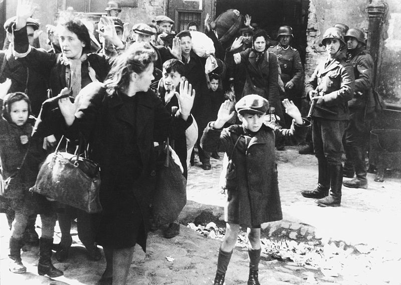 Nazis evicting the last remaining Jews in Warsaw from their homes for relocation to death camps, 1943. Via Wikimedia Commons.