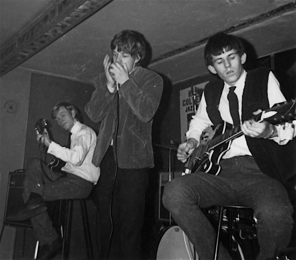 The Rolling Stones performing at Studio 51 Club in Great Newport Street, London, April 14, 1963. Brian Jones (left) and Keith Richards (right) would not play their guitars while sitting down for long, while Jagger would learn to get more animated on stage. (Photo by Mark and Colleen Hayward/Redferns)