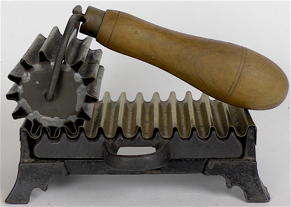 The 1887 Elgin hand fluter iron was heated by inserting a hot plug between the base of the iron and its lower fluted surface.