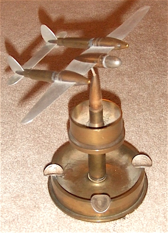 Worlds War II trench art ashtray from the Pacific Theater, depicting a P-38 with aluminum wings and tail. The cigarette rests are made of Australian coins dated 1944.